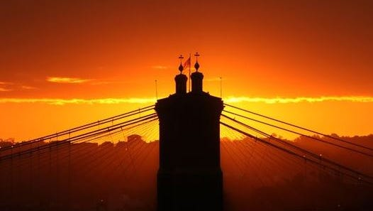 The John A. Roebling Suspension Bridge is in silhouette as the sun rises Wednesday. Photographed from the Covington side of the Clay Wade Bailey Bridge on Sept. 28, 2011.