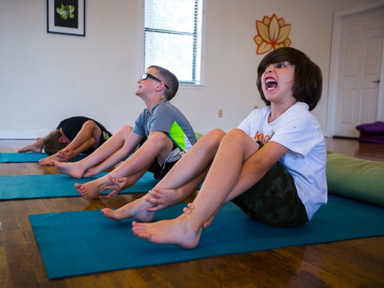 James Roegge, 7, right, engages in a yoga pose with