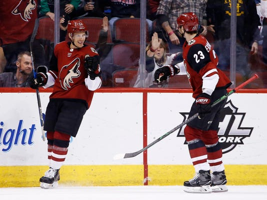 Arizona Coyotes center Nick Cousins (25) celebrates his goal against the New York Islanders with defenseman Oliver Ekman-Larsson (23) during the first period of an NHL hockey game, Monday, Jan. 22, 2018, in Glendale, Ariz. (AP Photo/Ross D. Franklin)