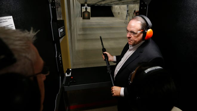 Republican Mike Huckabee, former Arkansas Governor, talks with staff members Tuesday, May 19, 2015, before firing off a Smith & Wesson AR M&P15 at the CrossRoads Shooting Sports indoor firing range in Johnston, Iowa.