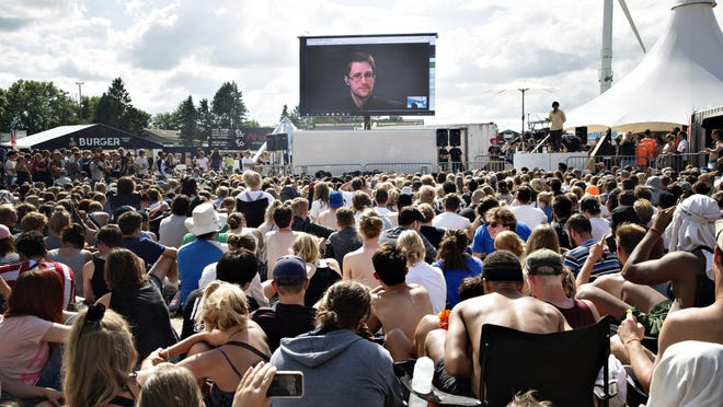 """Whistleblower Edward Snowden speaks from his exile in Russia on a giant screen in 2016 at the Roskilde Festival in Denmark. """"You are being watched all the time and you have no privacy,"""" he said."""