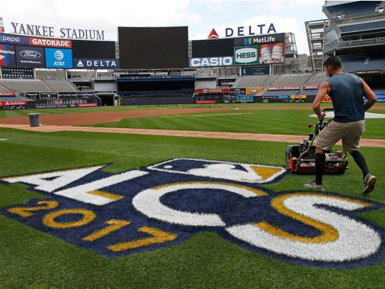A groundskeeper mows the grass around a recently painted