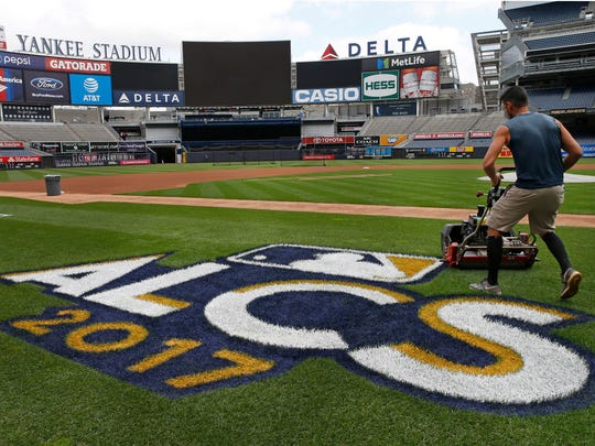 A groundskeeper mows the grass around a recently painted field logo before an American League Championship Series workout day at Yankee Stadium.
