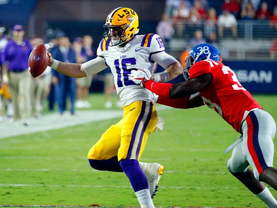 LSU quarterback Danny Etling (16) is knocked out of
