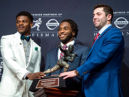 Heisman Trophy finalists, from left, Louisville quarterback Lamar Jackson, Stanford running back Bryce Love and Oklahoma quarterback Baker Mayfield pose with the trophy Saturday, Dec. 9, 2017, before the final selection in New York. (AP Photo/Craig Ruttle)