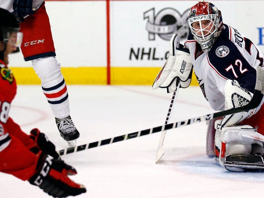 Columbus Blue Jackets goalie Sergei Bobrovsky, right, blocks a shot by Chicago Blackhawks left wing Ryan Hartman during the second period of an NHL hockey game Friday, March 31, 2017, in Chicago. (AP Photo/Nam Y. Huh)
