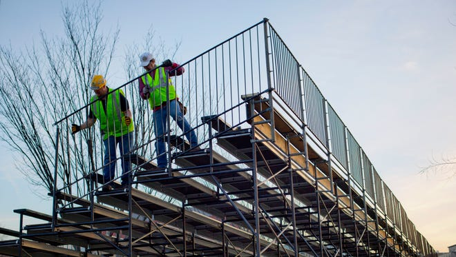 Workers on Friday install handrails for bench seating along Pennsylvania Avenue in front of the White House in Washington, D.C., as preparations continue for next week's Inauguration of President-elect Donald Trump.