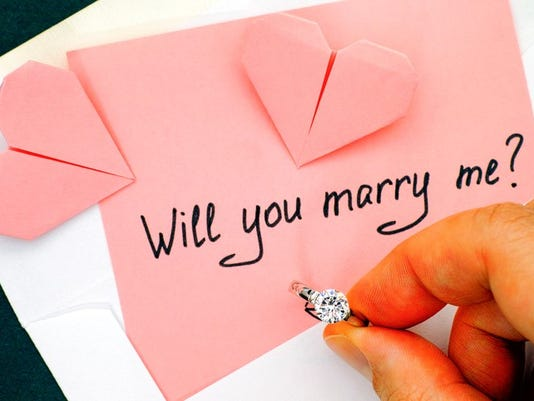 Woman hand holding engagement ring. Letter with text Will you marry me? in envelope and two origami hearts on the table.