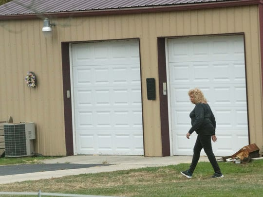 Peggy Foulke walks her property next to Charles Williams land where she has been in yearslong legal battle with other neighbors disputing he is running an auto garage out of his house.