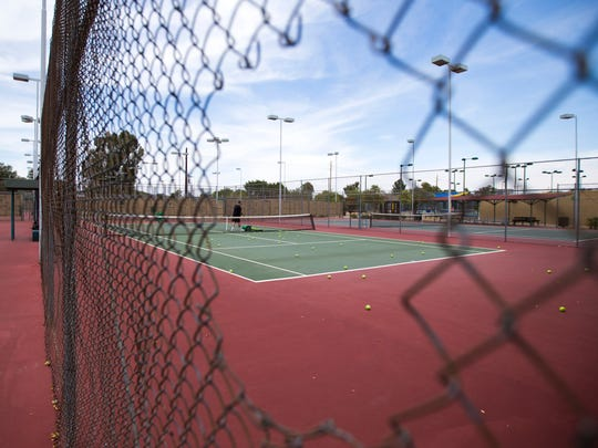 A tennis court is seen through a hole in a fence at the Phoenix Tennis Center on May 25, 2014.