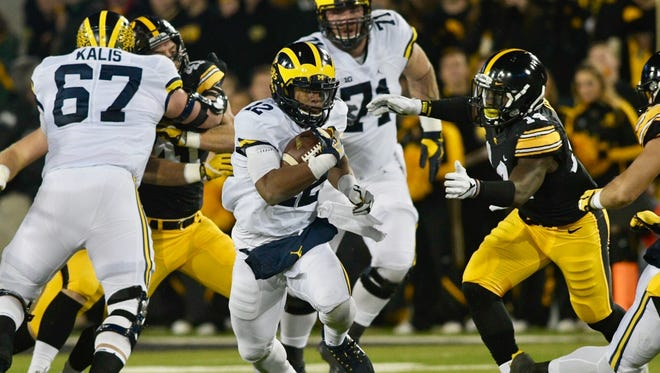 Michigan's Chris Evans finds a hole in the Iowa defensive line on Saturday night.