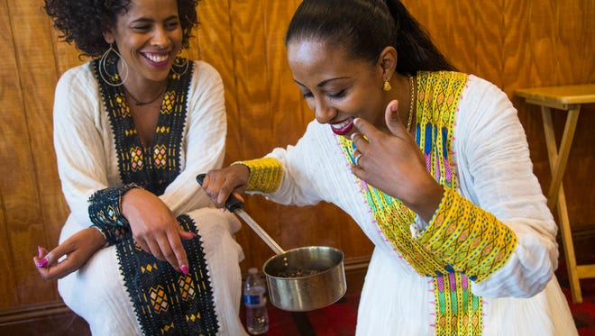 Selame Bru (left) watches Salem Beyene smell the freshly roasted coffee beans at Cafe Lalibela in Tempe, Ariz. May 30, 2017.
