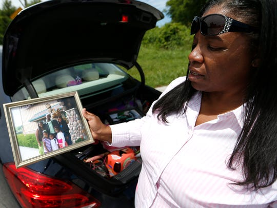 Angelina Hunley hold a photo of her dad C.L. Lewis