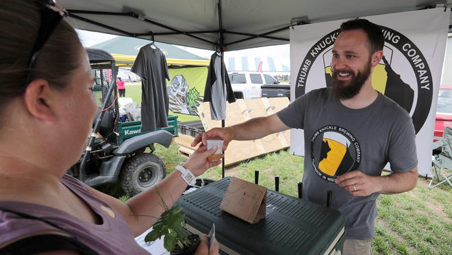 Thumb Knuckle Brewing co-owner Ed Thiry distributes beer samples Tuesday at the 2017 Wisconsin Farm Technology Days in Algoma. Thumb Knuckle uses Cascade hops grown by Fully Shire Hops N' Rocks of Algoma in its Heyder Helles and Boat Load IPA craft brews.