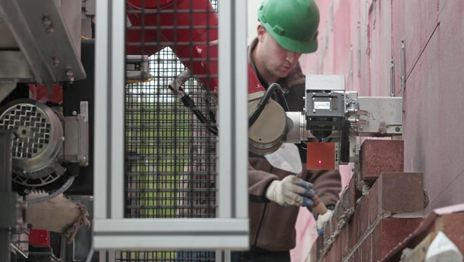 A brick-laying robot called SAM, or Semi-Automated Mason, lays down bricks as it constructs a wall at Construction Robotics in Victor. Working directly behind SAM is mason Nick Palem, who finishes each brick and checks the work for quality purposes.