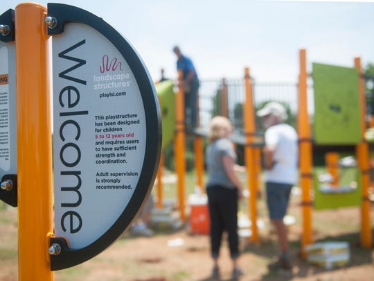 Volunteers work to build a playground in the East New Street Park in Glassboro on Saturday.