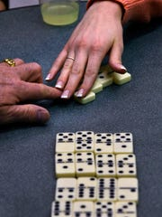 Players exchange dominoes in a game of 42 at The Grace Museum.