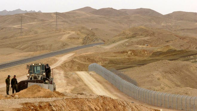 In this Feb. 15, 2012 photo, an Israeli bulldozer works at the site where Israel builds a barrier along the border with Egypt in southern Israel. Magal S3, the Israeli company that has built high-tech fences along the country's volatile borders is now trying to build a bridge to the Trump administration, hoping to use its experience to cash in on his plan to seal the border with Mexico.