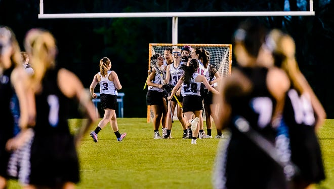 Members of the Okemos Girls Lacrosse team celebrate at mid-field after their win over Haslett-Williamston in the CAAC lacrosse championship game Friday May 12, 2017 in Okemos.  KEVIN W. FOWLER PHOTO