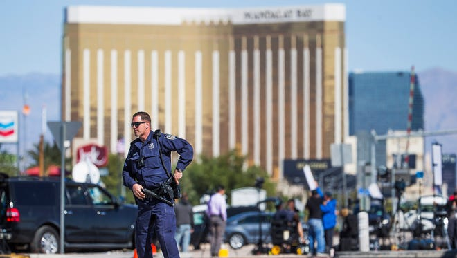 Oct 2, 2017; Las Vegas, NV, USA; Nevada Highway Patrol trooper Jones (no first name given) stands at a roadblock on Las Vegas Blvd. and Sunset Road with Mandalay Bay in the background Monday morning.  At least 58 people were shot to death at a country music concert near Mandalay Bay, Sunday evening.  Mandatory Credit: