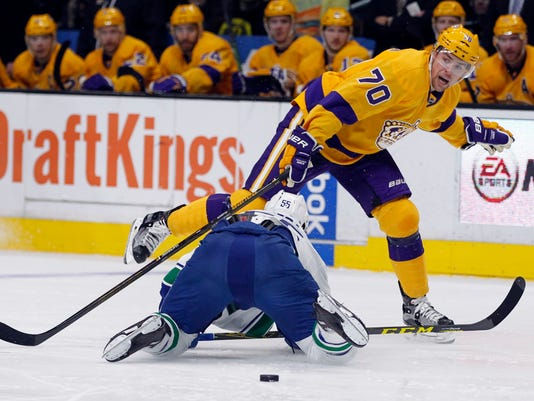 Los Angeles Kings left wing Tanner Pearson (70) calls out for a teammate as Vancouver Canucks defenseman Alex Biega (55) defends during the second period of an NHL hockey game in Los Angeles, Monday, March 7, 2016. (AP Photo/Alex Gallardo)