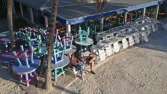 In this photo provided by the Florida Key News Bureau, two employees of the Morada Bay Cafe in Islamorada, Fla., sit on chairs usually occupied by visitors. The chairs and tables have been removed from the restaurant's beach due to the coronavirus crisis that has resulted in local government directives to shut down Florida Keys tourism facilities, including lodging entities.
