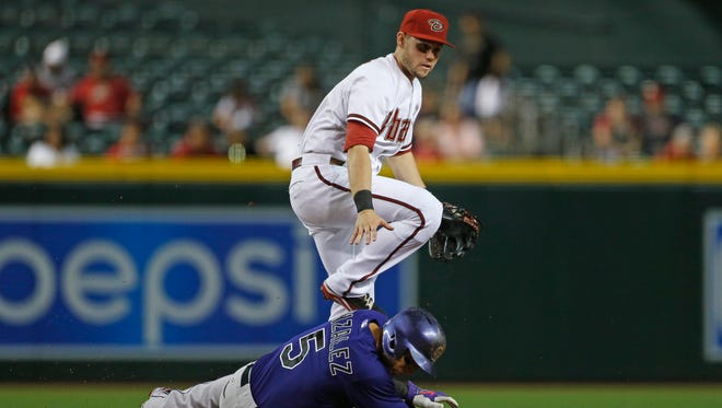 Diamondbacks' Chris Owings (16) throws to first for a double play after an out on Rockies' Carlos Gonzalez (5) at Chase Field in Phoenix, AZ on April 27, 2015.