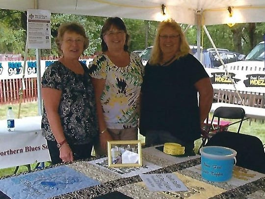 """Pictured are sisters Diana Stritzel, from left, Donna Grenwalt and Doris Breidel, and they would like to thank all who supported their one-day raffle, which they held on Aug. 20, at the 25th annual """"Big Bull Falls Blues Fest."""" A quilt, made of 12 consecutive years of """"Blues Fest"""" t-shirts, was raffled off in honor of their late brother, Daniel Merkes of Edgar, who was a huge """"Blues Fest"""" supporter. After the raffle, $890 was raised, with the money being donated to the Friends of the Mead Wildlife Area."""