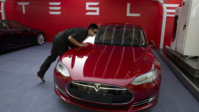 A worker cleans a Tesla Model S sedan in Beijing. Tesla Motors Inc. may have picked Northern Nevada as a location for a factory to build batteries for its electric cars.  AP file FILE - In this April 22, 2014 file photo, a worker cleans a Tesla Model S sedan before a event to deliver the first set of cars to customers in Beijing. Tesla Motors Inc. reports quarterly financial results on Thursday, July 31, 2014. (AP Photo/Ng Han Guan, File)