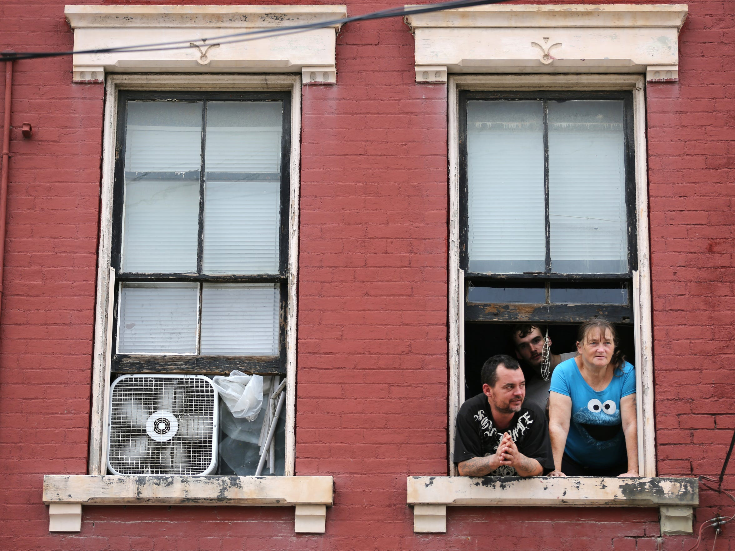 Rick Davis, left, and his son, Brandon, 18, and wife, Debbie, look out the window from their home on State Street in Lower Price Hill. The family has lived in Lower Price Hill their entire lives.