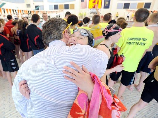 Dallastown's Alyssa Bixler is embraced by her coach,