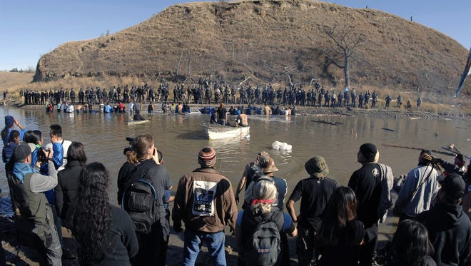 Dakota Access Pipeline protesters, foreground, stand in the waist-deep water of the Cantapeta Creek, northeast of the Oceti Sakowin Camp, near Cannon Ball, N.D., this month.