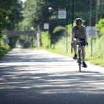 Hattiesburg native and author Benjamin Morris rides his bike down the Longleaf Trace at his stop in Hattiesburg on Friday. Morris is on a three-week, 500-mile biking journey across Mississippi in opposition of House Bill 1523.