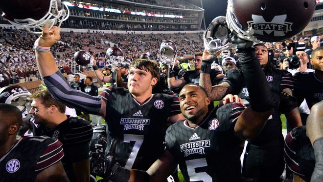 Mississippi State quarterback Nick Fitzgerald (7) and defensive back Cedric Jiles (5) celebrate after the game against the Kentucky Wildcats at Davis Wade Stadium. Mississippi State won 42-16.