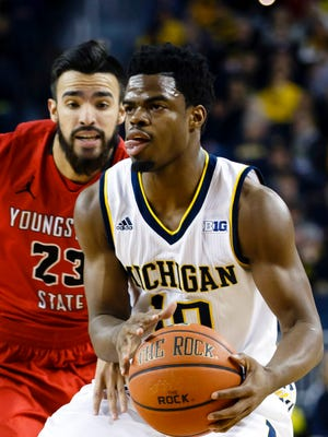 Michigan guard Derrick Walton Jr. (10) moves the ball on Youngstown State guard Francisco Santiago in the first half of the 105-46 win Saturday at Crisler Center.