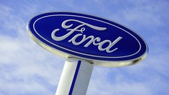 The Ford logo is seen on a sign at a dealership in