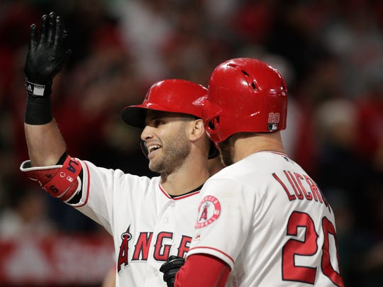 Los Angeles Angels' Tommy La Stella and Jonathan Lucroy, front, celebrate a three-run home run by La Stella during the first inning of the team's baseball game against the Milwaukee Brewers, Tuesday, April 9, 2019, in Anaheim, Calif. (AP Photo/Jae C. Hong)