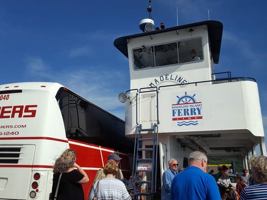 A Lamers tour bus and passengers ride on the Madeline Island Ferry.