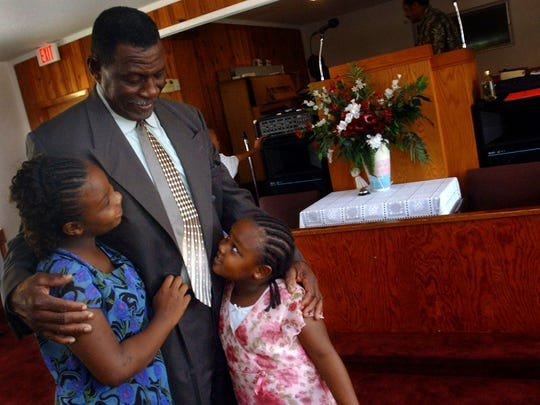 Elder Charlie Jones, of Wabasso's Church of God by Faith, hugs Alteria Woods (left), then 9, and Alesus Woods, 4, before church service begins on Sunday, Oct. 5, 2005. Alteria Woods was killed Sunday, March 19, 2017, in an exchange of gunfire involving the Indian River County Sheriff's Office SWAT team in a drug raid in Gifford. She was 21.