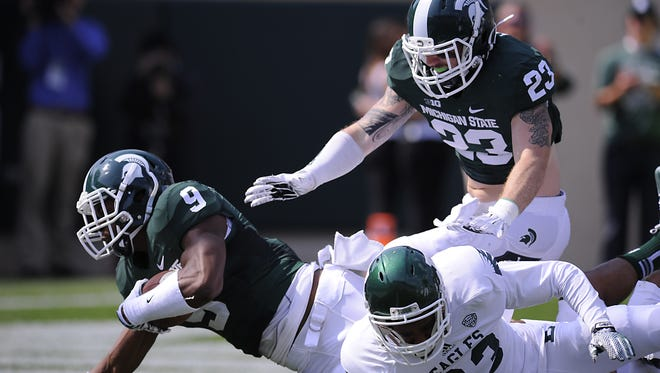 MSU's  Montae Nicholson recovers an Eastern Michigan fumble in front of teammate Chris Frey (23) in the second half on Saturday at Spartan Stadium. Both are true freshmen who played significant snaps in the 73-14 victory.