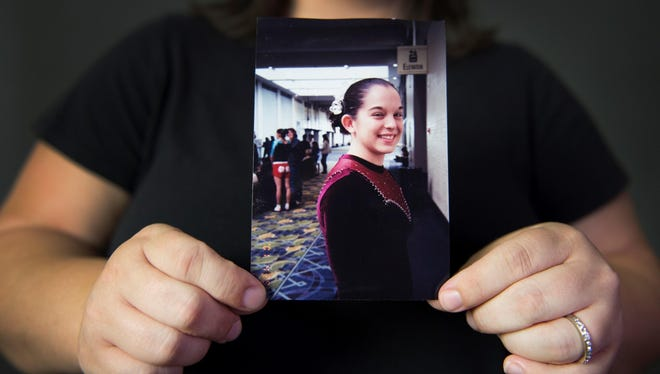 Kelly Cutright, who was abused by her gymnastics coach as a young teen and asked to be identified with her maiden name, holds a photo of herself as a gymnast when she was 15.