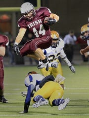 Aquinas' Billy Lombardi, top, hurdles Sweet Home's Jorden Johnson at the line of scrimmage during 2011 Class A state regionals.