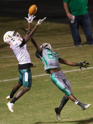 Fort Myers High School's Milan Tucker breaks up a pass to Dunbar's Shocky Jacques-Louis during first period play Friday at Edison Stadium in Fort Myers.
