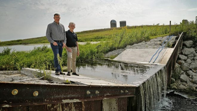 Shawn Richmond and Professor William Crumpton stand on a spillway of a pilot drainage project near Gilmore City Thursday, Aug. 27, 2015.