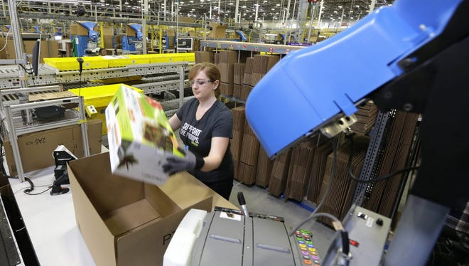 In this Feb. 13, 2015 file photo, a worker places an item in a box for shipment in DuPont, Wash. On Monday, Amazon made changes to its parental leave policy for all new parents.