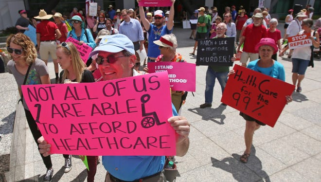 People march during a protest against the Republican bill in the U.S. Senate to replace President Barack Obama's health care law Tuesday in Salt Lake City.