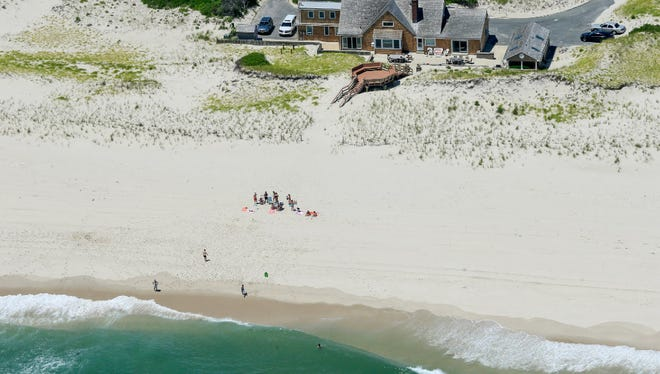 "In this Sunday, July 2, 2017, photo, New Jersey Gov. Chris Christie uses the beach with his family and friends at the governor's summer house at Island Beach State Park. Christie defended his use of the beach, closed to the public during New Jersey's government shutdown, saying he had previously announced his vacation plans and the media had simply ""caught a politician keeping his word."""