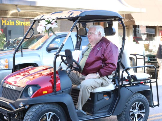 Bob Cowan driving his golf cart through the Christmas parade.