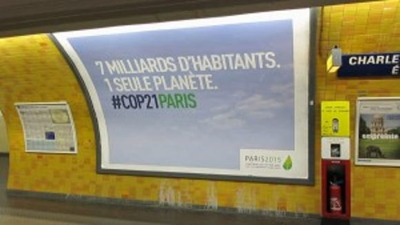 "COP 21 sign in Paris subway, ""Seven billion inhabitants. One single planet."" ""Milliard"" means a thousand millions (a billion) in English.]"