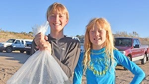 Harley Richardson, left, and her brother Luther, of Lemitar, showed up to help stock more than 100,000 largemouth bass at Elephant Butte Lake. Bill Evans was also stocked with some bass.